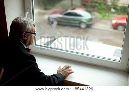 Old Man In Black Suit Looks Through The Window