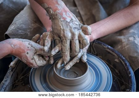 Woman and man hands. Potter at work. Creating dishes. Potter's wheel. Dirty hands in the clay and the potter's wheel with the product