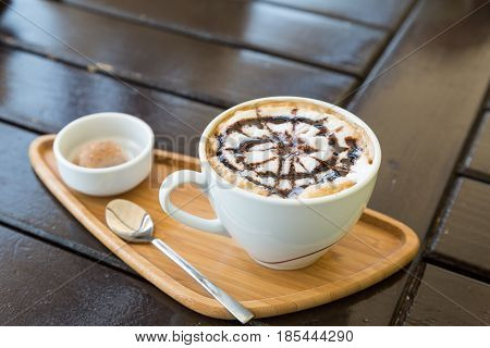 Cappuccino with biscuit on wood on the table