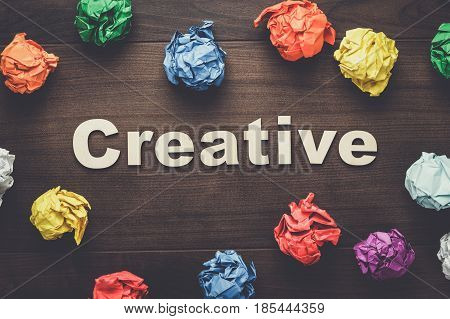 word creative and crumpled colorful paper. word creative on wooden background. creative concept. wooden letters forming word creative