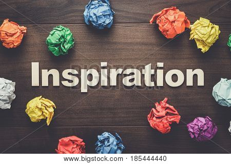 word inspiration and crumpled colorful paper. word inspiration on wooden background. inspiration concept. wooden letters forming word inspiration