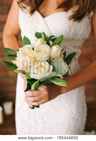 Bride in a white elegants lacy wedding dress holding a flowers bouquet from white fresh rose in hands. Wedding bridal bouquet close up. Tenderness, love, wedding, fashion - concept.