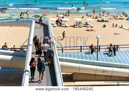 Alicante Spain - April 17 2017: People walking along the footbridge and view to the Postiguet Beach of Alicante city. Alicante is a main resort city on the Costa Blanca. Spain