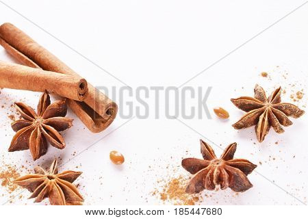 anise stars with cinnamon sticks over white background copy space