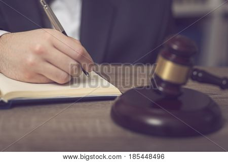 Detail of a judge sitting at his desk studying new laws and legislation and taking notes. Selective focus