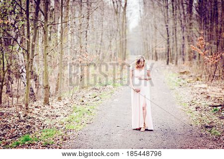 Pregnant Woman Outdoors Relaxing In Forest