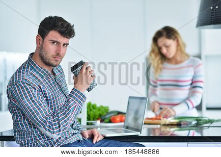 Couple standing and sitting at the kitchen while smiling and man reading a newspaper and holding mug before work