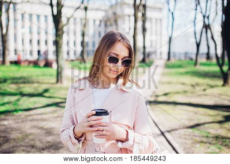 Fashionable woman with phone and cofee in the city.