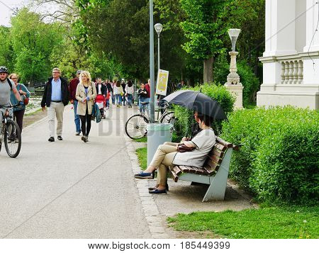 CLUJ-NAPOCA ROMANIA - MAY 1,  2017: People walk and relax in the park on a cloudy day.