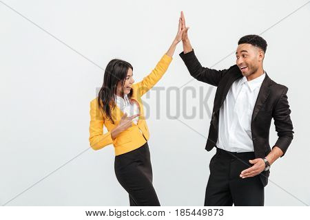 Picture of happy colleagues business team standing over white background isolated. Looking aside gives a high-five to each other.
