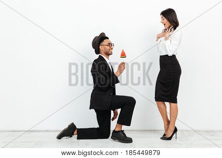 Picture of happy african business man gives an ice cream to his colleague woman standing over white background isolated. Looking aside.