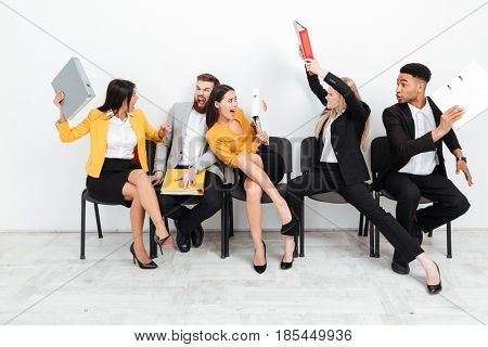 Image of screaming angry colleagues sitting with folders and fighting. Looking aside.