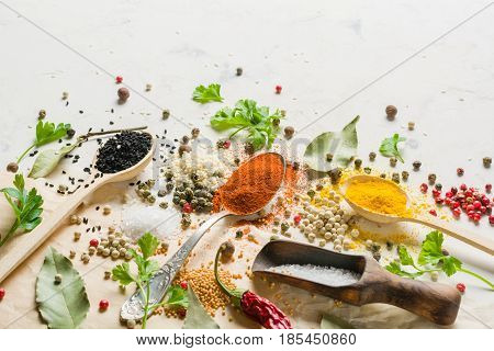 Spices In Different Spoons On A Stone White Background. A Scattering Of Spices.