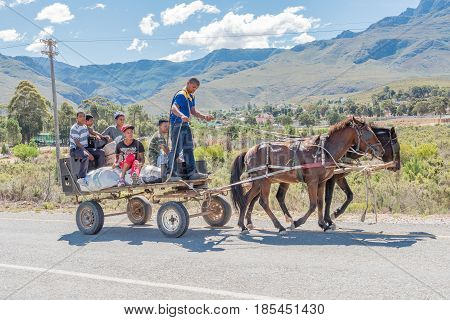 GENADENDAL SOUTH AFRICA - MARCH 27 2017: Unidentified people on a horse drawn carriage at the entrance to Genadendal the first mission station in South Africa founded 1738