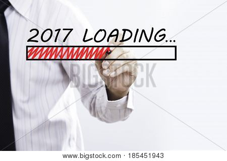 Businessman hand writing New Year 2017 Loading with red marker on transparent wipe board business concept.