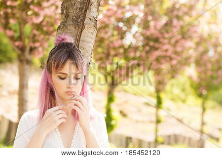 Girl with colored hair. A woman with pink hair poses near sakura. A woman dressed in a white dress and a denim jacket. Portrait of a woman with flowers. Blooming tree