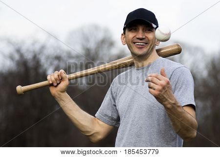 Portrait of happy smiling baseball player outdoors.