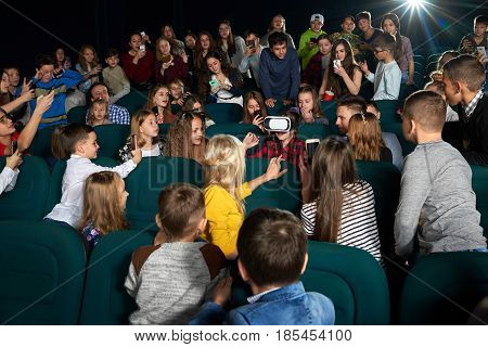 Young boy wearing virtual reality glasses his friends surrounding him at the movie theatre background technology people fun modern device gadget 3D headset leisure positivity concept.