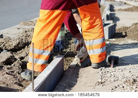 Repair of the sidewalk. Professional working masons in overalls lay curbs before laying stone paving slabs