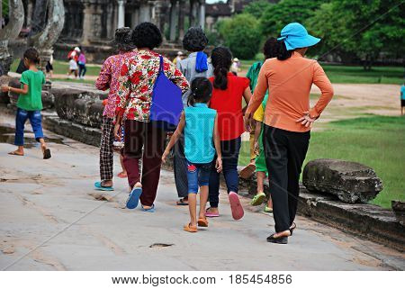 A group of women and children walking in Ankor Wat. Cambodia
