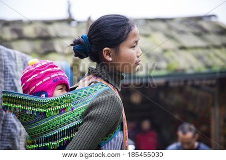 Sa Pa, Vietnam - 12 March, 2017:  Unidentified ethnic Hmong minority woman carries her little baby on her back in the village of Cat Cat near Sa Pa, Northern Vietnam