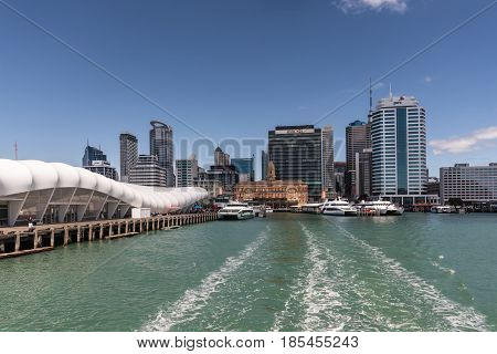 Auckland New Zealand - March 3 2017: Ferry building and pier seen from greenish water with city skyline in background under blue sky. Ferries at docks.