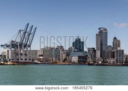 Auckland New Zealand - March 3 2017: Row of container cranes at Commercial Harbor with part of city skyline in back under blue sky and behind greenish ocean water. Highrise buildings. No ships.