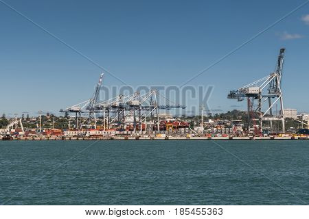 Auckland New Zealand - March 3 2017: The container terminal with its cranes and boxes under blue sky and behind greenish ocean water. War Memorial Museum on hill in background.