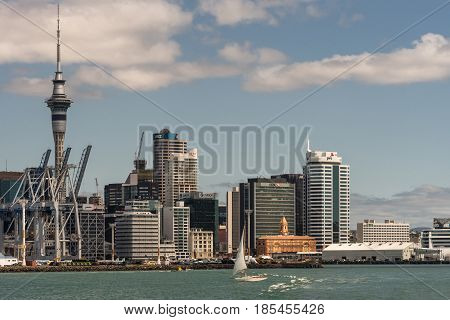 Auckland New Zealand - March 3 2017: Container terminal with its cranes under blue sky and behind greenish ocean water. City skyline with ferry terminal and office towers as background. White sailing boat on the water.
