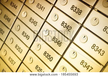 Safety deposit box wallpaper. Numerous secure safety deposit boxes with lock and number plate. Gold metal. Insurance banking concept.