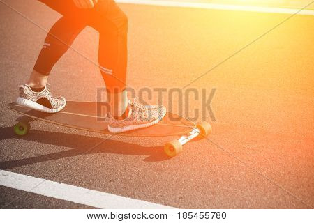 Man riding on longboard on road. Fitness or sport man resting and relaxing outdoors. Action shot of alongboarder skating on urban road. Toned.