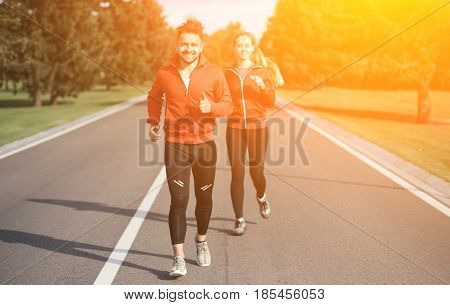 Sport man and woman jogging along road. Beautiful couple in red jackets training and looking at camera. Fitness concept. Toned.