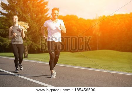 Fitness couple. Young man and woman jogging in nature. Happy man and woman smiling for camera and doing sport. Toned.