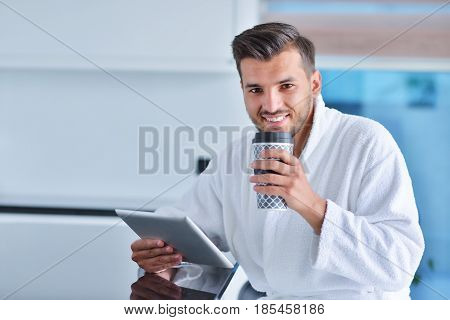 Happy man using digital tablet while having coffee in kitchen.