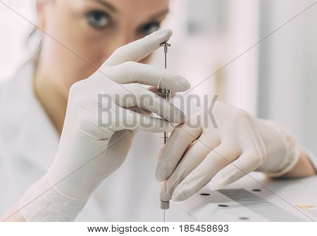 Portrait of female researcher doing research in a chemistry lab. Gas chromatograph analyzer