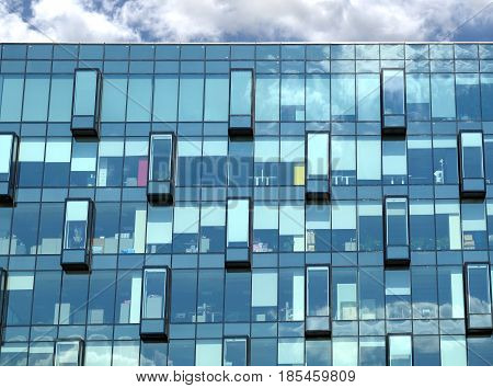 Facade with glass wall of modern office building with many large panoramic windows in business cluster under blue sky with clouds front view close-up