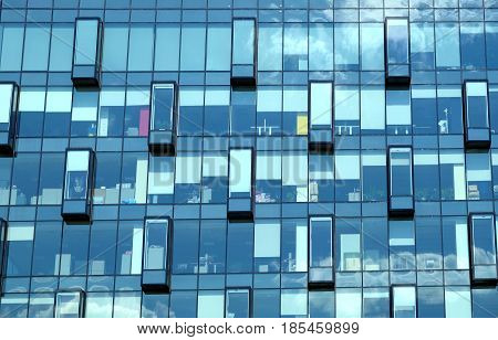 Facade with glass wall of modern office building with many large panoramic windows in business cluster front view close-up
