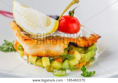 Baked perch fillet with tomato lemon and vegetables on white plate. Close up image with selective focus.