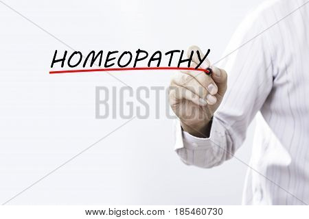 Businessman hand writing homeopathy with red marker on transparent wipe board business concept