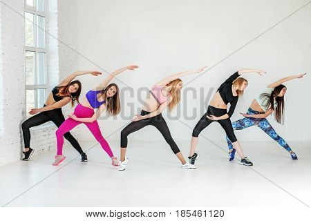Young girls involved in fitness at the gym. The concept of sports dance yoga and healthy lifestyle.
