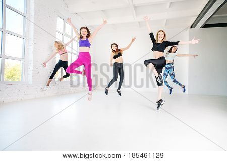 Young girls dancing in the gym. Jump. The concept of sport dance and a healthy lifestyle.
