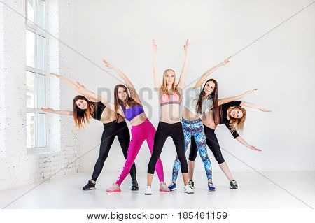 Group conducts training in the gym. The concept of sports dance yoga and healthy lifestyle.
