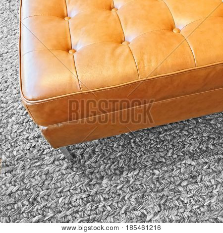 Close-up of a leather seat on gray wool carpet. Modern design.