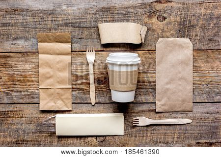 food delivery service workdesk with paper bags and plastic cup on restourant wooden table background top view mockup
