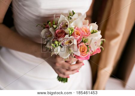 Bride and groom holding bridal bouquet close up. red and white roses, freesia, brunia decorated in composition.