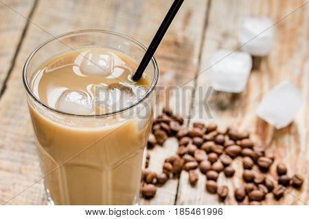 Ice coffee with milk and beans for lunch on wooden table background