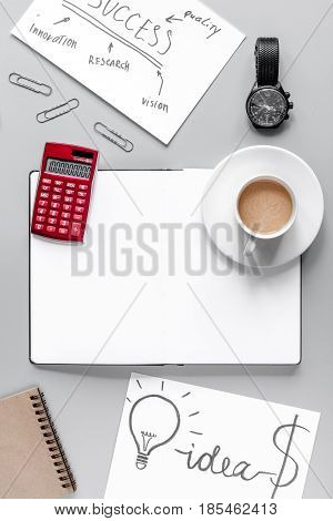 workplace in office with business plan development with copybook and cup of coffee on gray desk background top view space for text