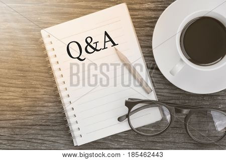 Concept Q&A message on notebook with glasses pencil and coffee cup on wooden table.