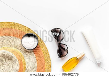 Summer cosmetic set with protection cream and hat on white background top view mock up
