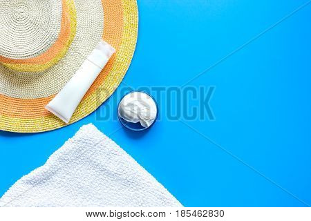 Summer cosmetic set with protection cream and hat on blue background top view mock up